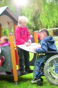 Enfant en chaise roulante sur une place de jeu inclusive